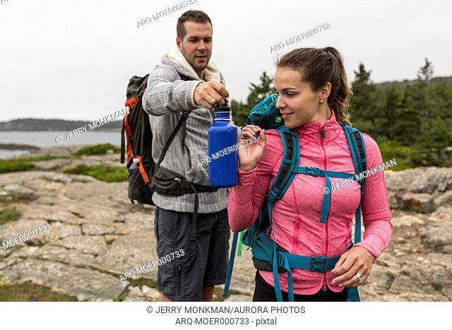Couple hiking on cloudy morning at Sand Beach in Acadia National Park, Maine, USA