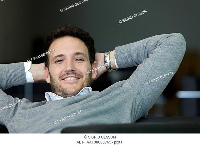 Man relaxing with hands behind back