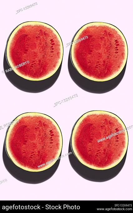 Four watermelon halves on a pink background