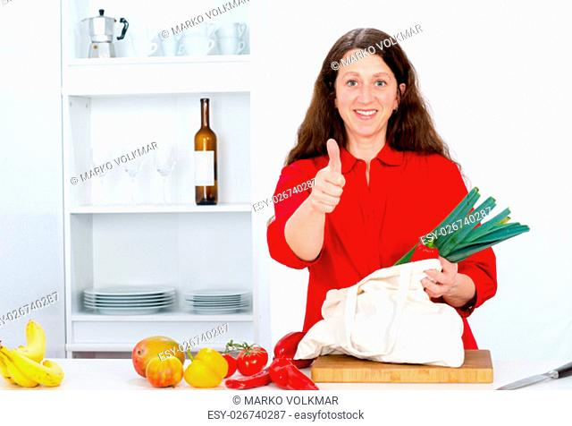 dark haired woman with thumb up in the kitchen