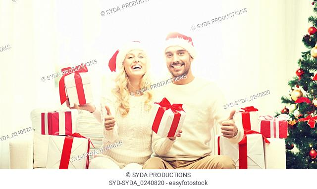 happy couple with christmas gifts and thumbs up
