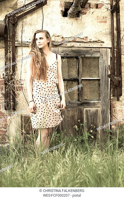 Young woman standing in front of an old garden shed