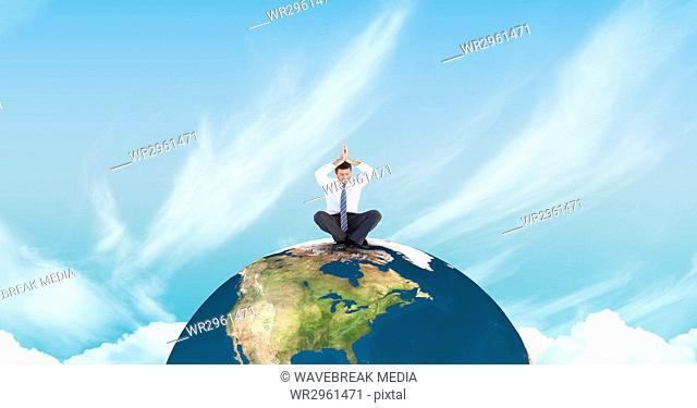 Businessman meditating on earth against sky