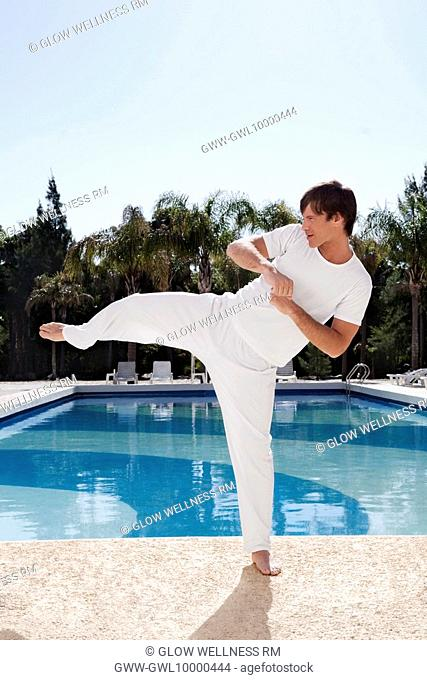 Man exercising at the poolside