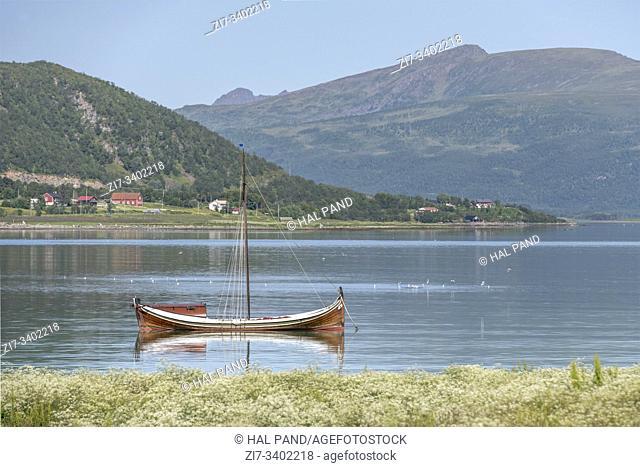 traditional wooden sailboat moored in fjord, shot under bright summer light near Strand, Andoya, Vesteralen, Norway