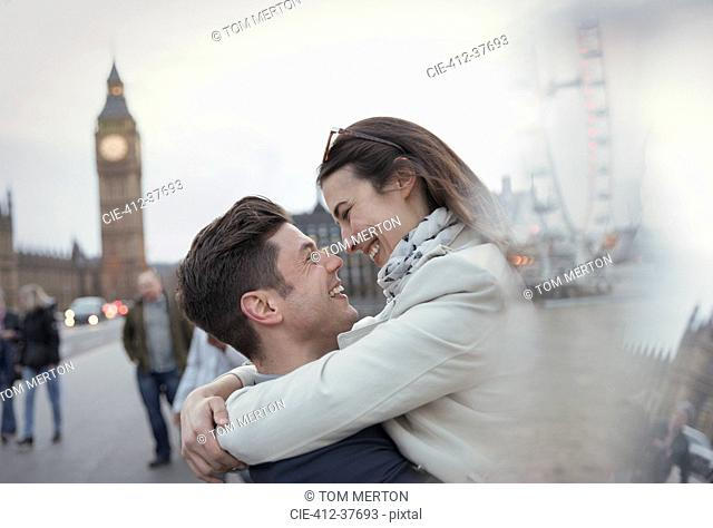 Romantic, affectionate couple tourists hugging near Big Ben, London, UK