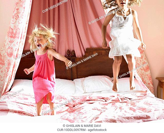 Girls jumping on a bed