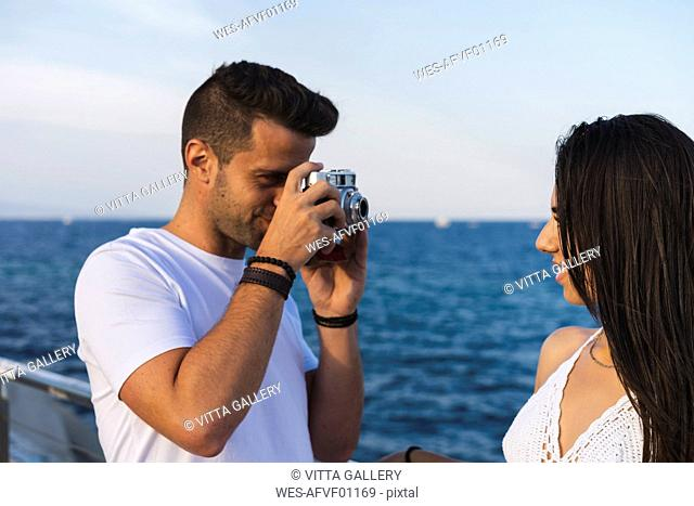 Young urban couple taking pictures by the sea