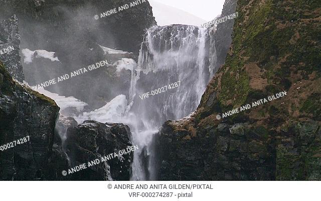 Hard wind blowing over waterfall