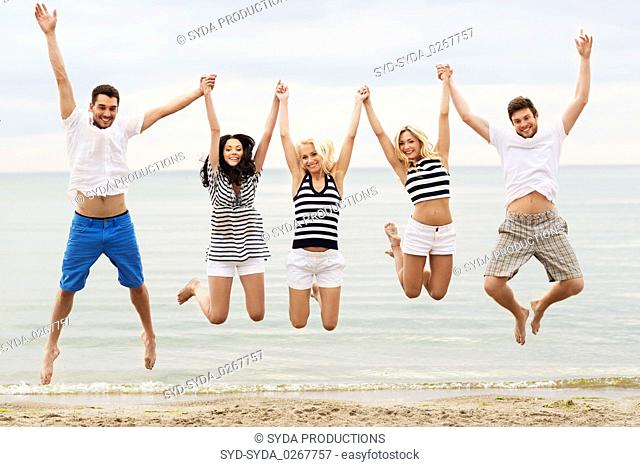 friends in striped clothes running along beach