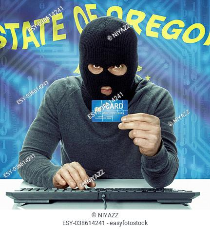 Dark-skinned hacker with credit card and USA states flag on background - Oregon