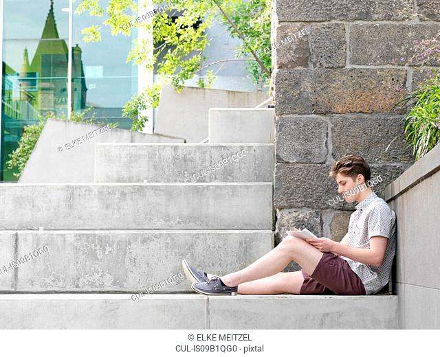 Young man sitting on step, outdoors, writing in notepad