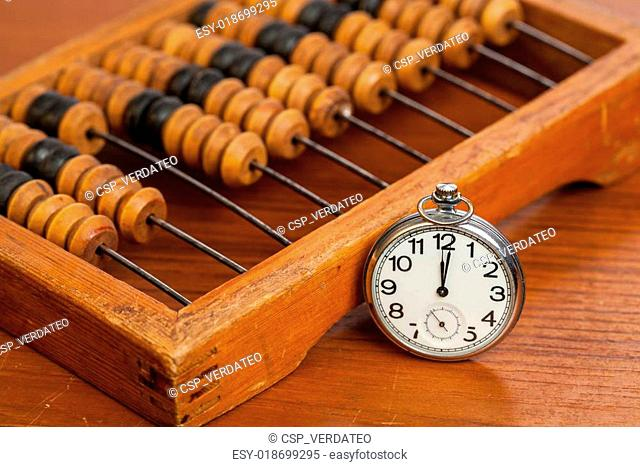 Pocket watch on table andt wooden abacus