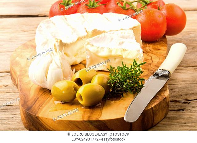 camembert with green olive, tomato, garlic and thyme on a wooden board