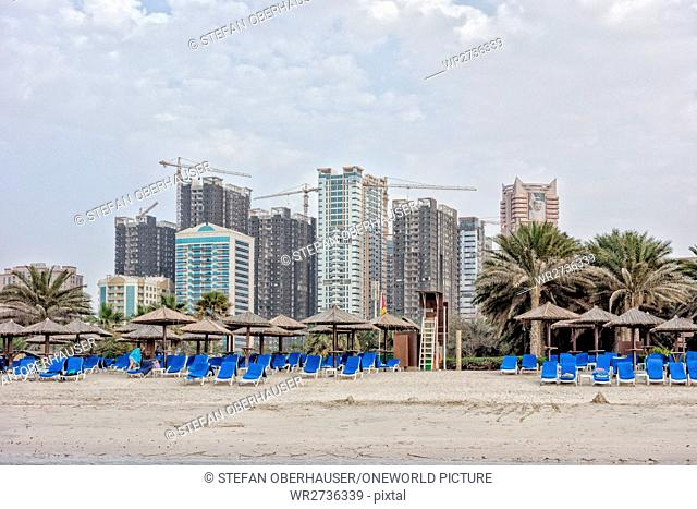 United Arab Emirates, Ajman, beach section in front of a large construction site in Sharjah