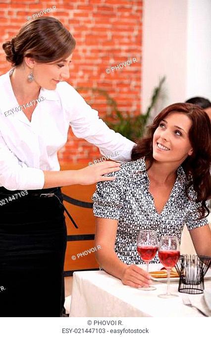 Waitress serving female customer