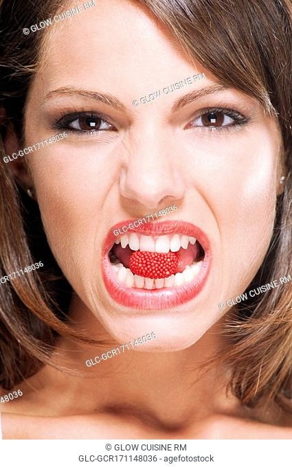 Portrait of a woman biting a raspberry