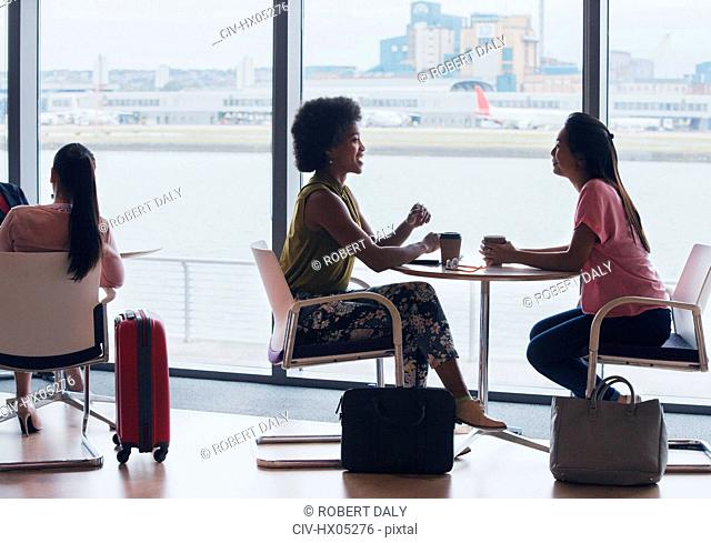 Businesswomen talking and drinking coffee in airport business lounge