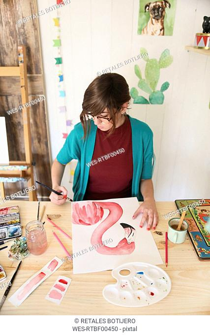 Woman painting aquarelle of a flamingo on desk in her studio