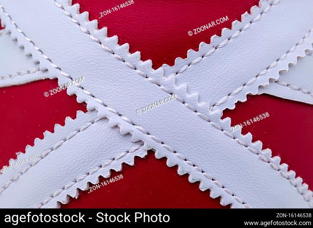 Fragment of red and white sneaker fabric. The texture of the material of sports shoes