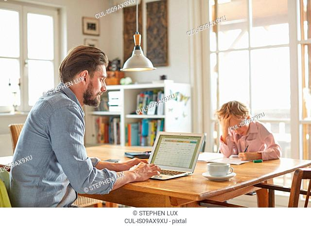 Father and son working in home office