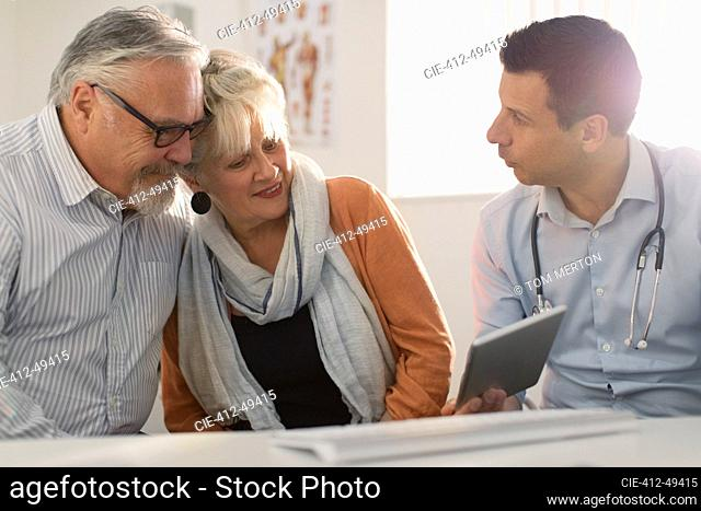 Male doctor with digital tablet meeting with senior couple in doctors office