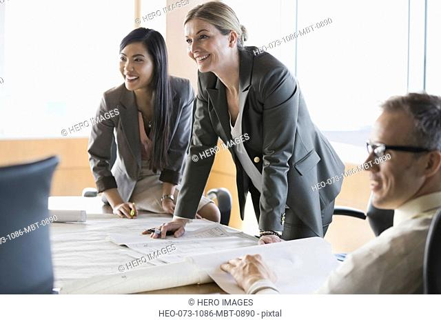 Business people reviewing blueprints in conference room
