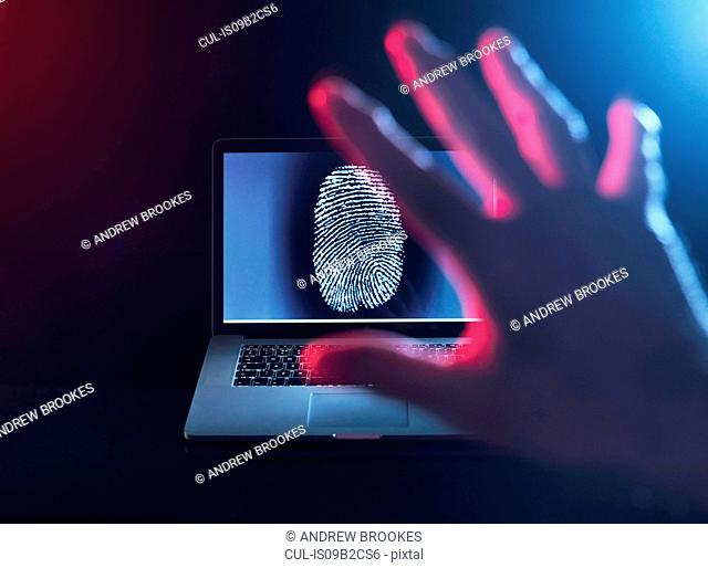 Computer Security, a finger print on a laptop illustrating a personnel password which is about to be hacked