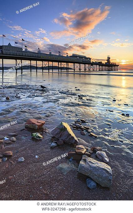 Rocks on the beach provide the foreground interest in this image featuring Paignton Pier which was captured at sunrise