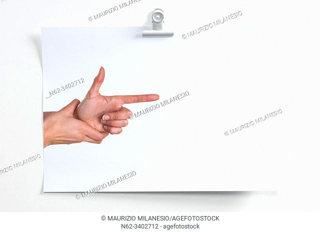 Blank sheet hanging on the wall with image of hands simulating a gun that shoots