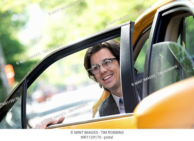 City life. People on the move. A young man in the back seat of a taxi