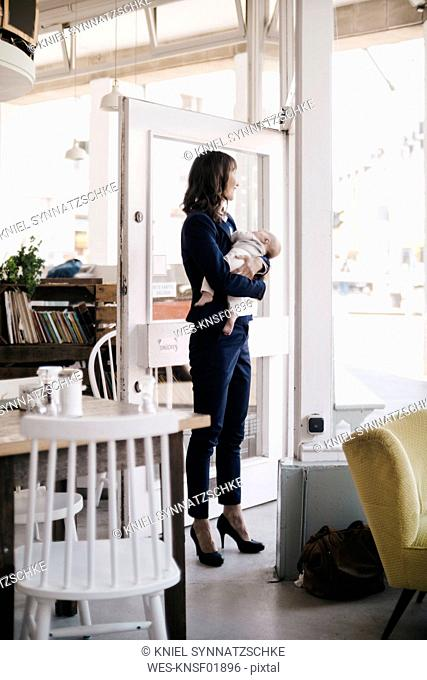 Businesswoman in cafe holding sleeping baby