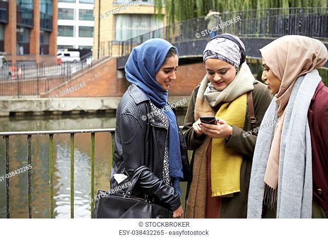 Muslim Female Friends Using Mobile Phone In Urban Setting