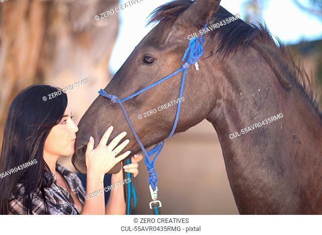 Young woman kissing horse's nose