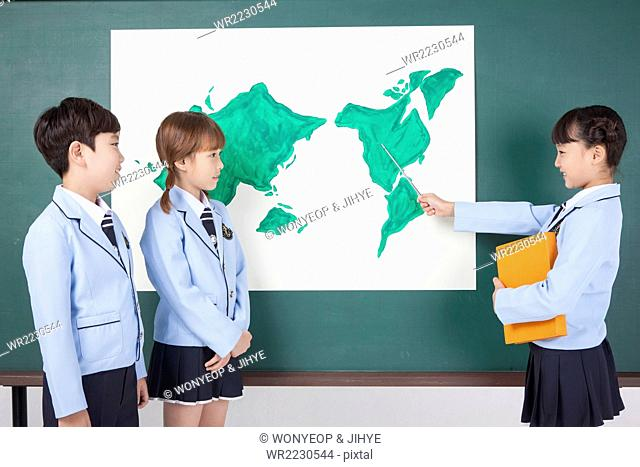 Three elementary school students in school uniforms standing in front of the blackboard and one of them pointing with a stick on the map on the blackboard