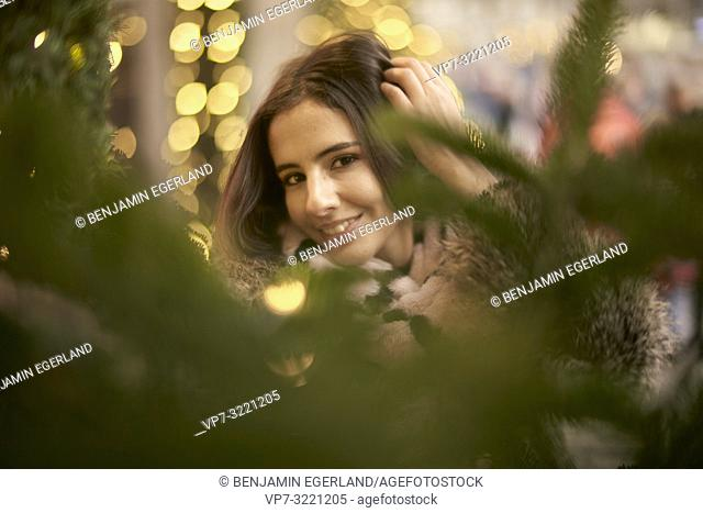 portrait of playful young woman behind lights of Christmas tree, in city Munich, Germany