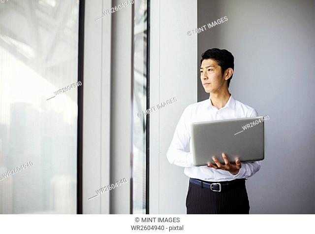 A businessman in white shirt holding a laptop and looking out of a window in a building