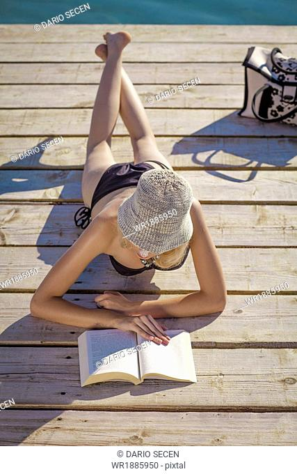 Croatia, Young woman with straw hat reads book on boardwalk