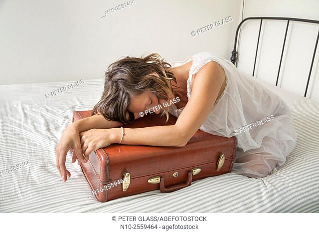 Young woman leaning on her suitcase