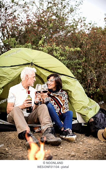 Senior couple sitting at campfire with wine in a tent