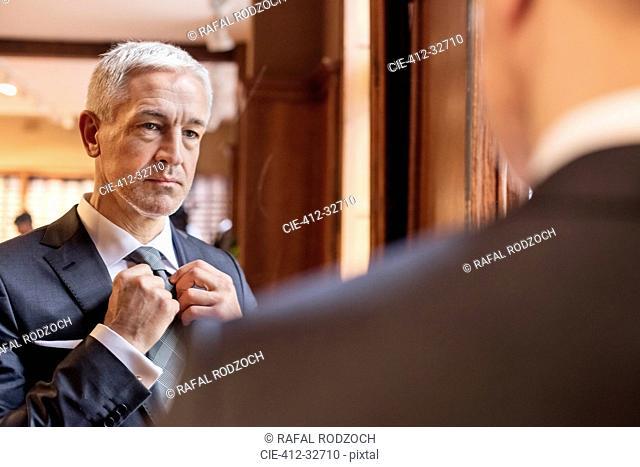 Businessman trying on tie in mirror in menswear shop