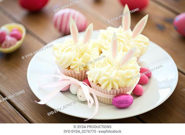cupcakes with easter eggs and candies on table
