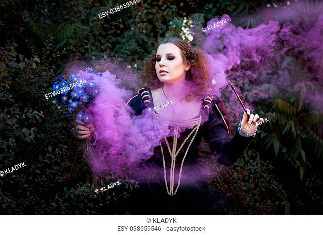 Woman showing tricks with a magic wand. She bewitched a bouquet of flowers from which it is purple smoke