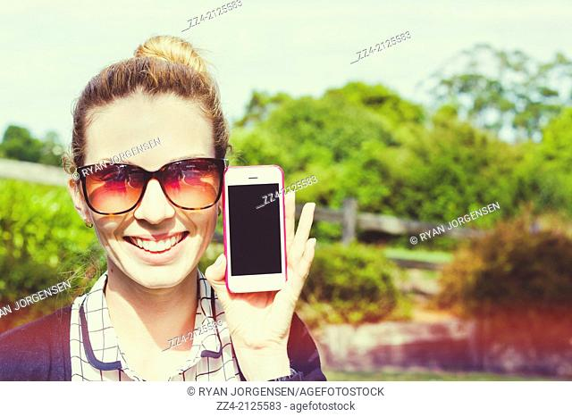 Quirky retro toned portrait of a smiling person holding and showing cell phone handset at green Australian outback location. Rural mobile apps