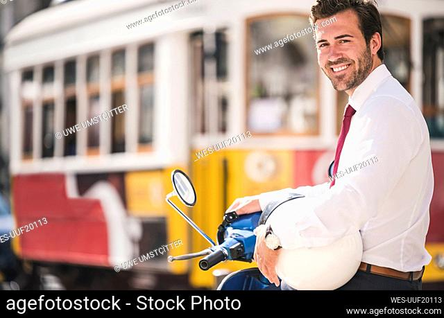 Portrait of smiling young businessman on motor scooter in the city, Lisbon, Portugal