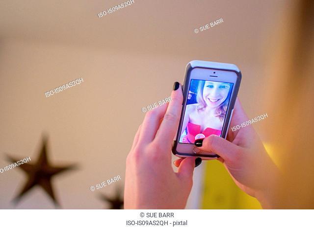 Hands of young woman taking smartphone selfie