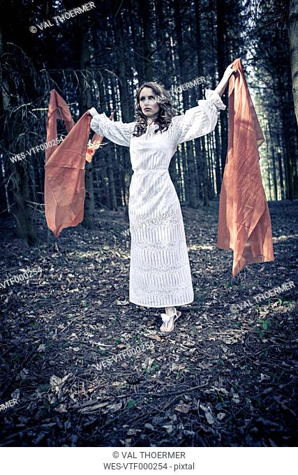 Portrait of a young woman standing in forest with outstretched arms holding clothes
