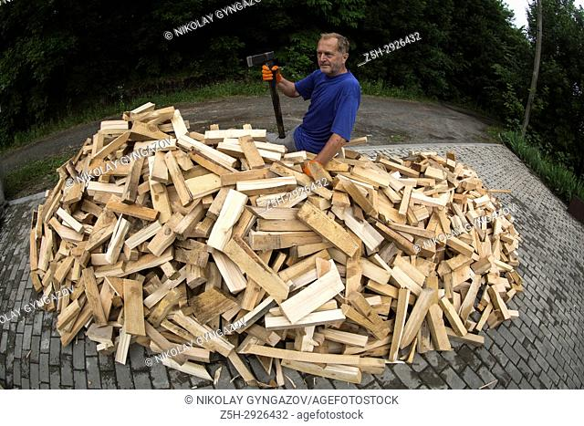 Man and a pile of staked firewood