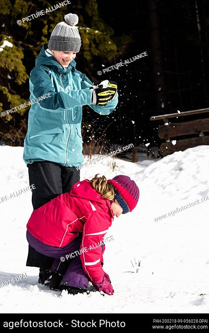 """14 February 2020, Lower Saxony, Braunlage: Levke (l) and Clara play with snow at the Wurmberg in the Harz Mountains. (to dpa """"""""Winters are getting warmer and..."""