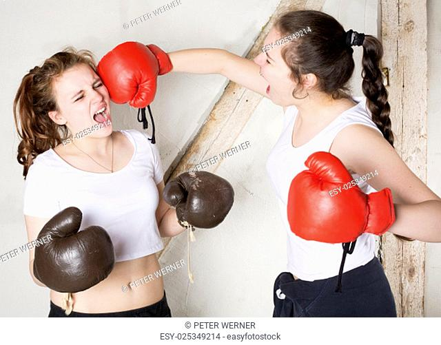 two young girls dressed as boxers are fighting